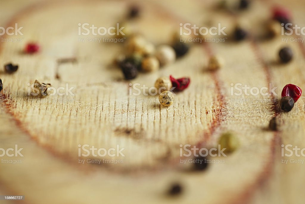 macro Mixed pepper, pink, black, white, green on  wooden board royalty-free stock photo