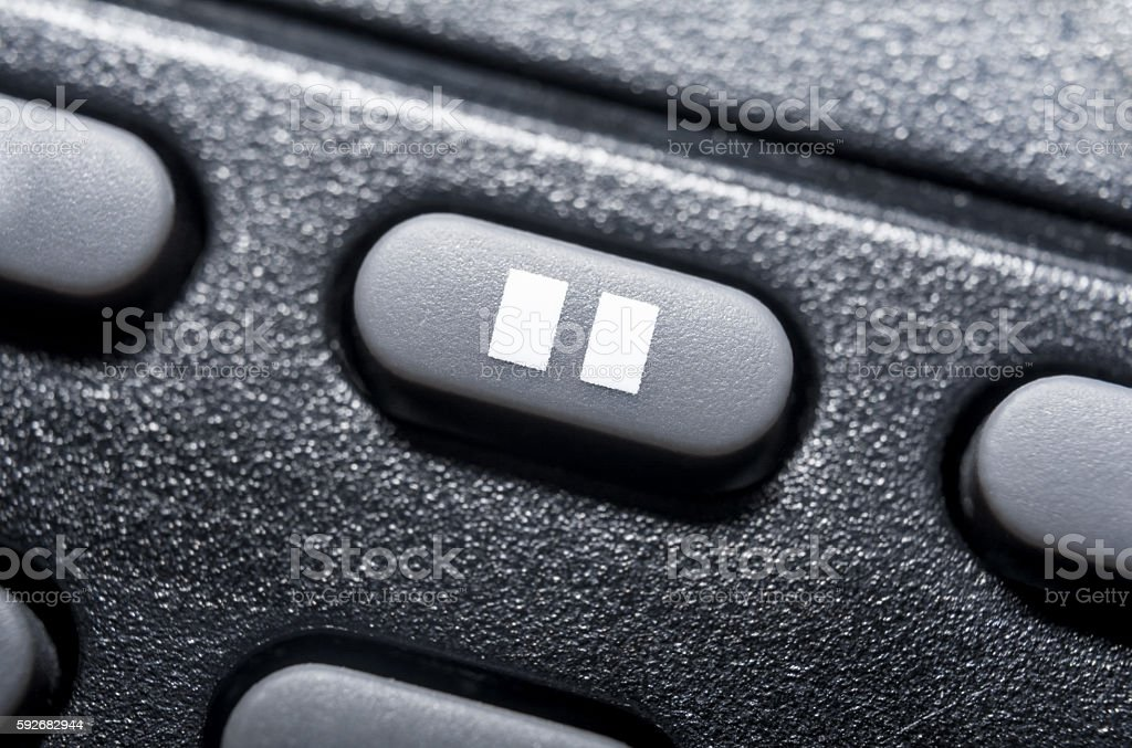 Macro Of A Black Pause Button On Black Remote Control stock photo
