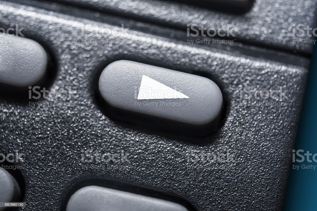 Macro Of A Black Play Button On Black Remote Control stock photo