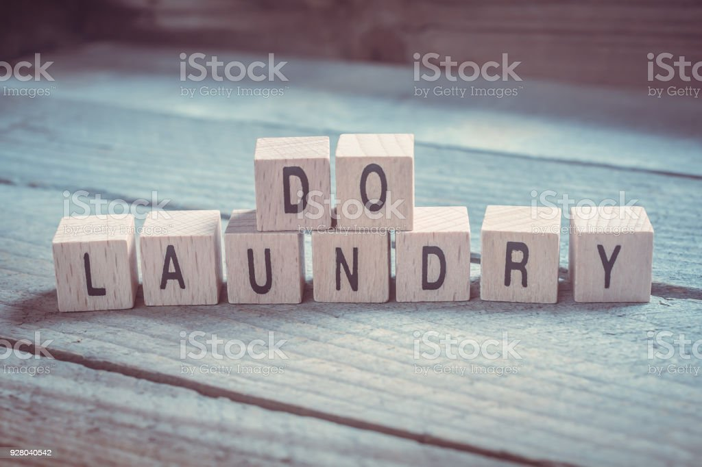 Macro Of A Do Laundry Reminder Formed By Wooden Blocks On A Wooden Floor stock photo