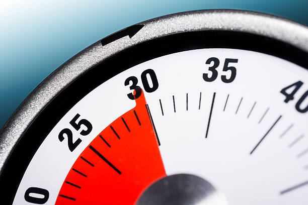 macro of a kitchen egg timer - 30 minutes - number 30 stock photos and pictures