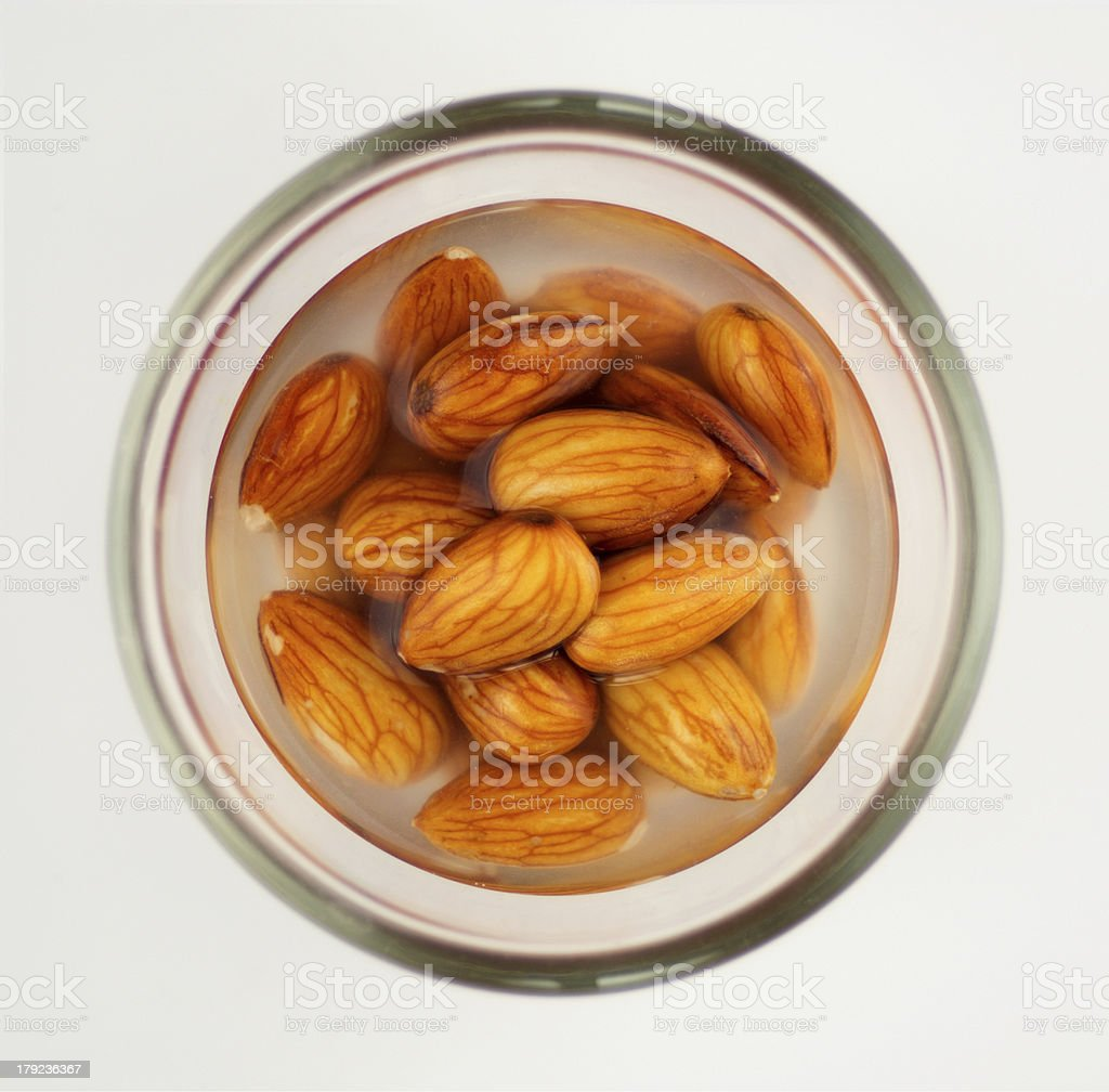 Macro of almonds soaking in water isolated on white stock photo