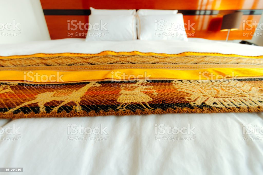 Macro of bed of a hotel room in Peru with typical bedding