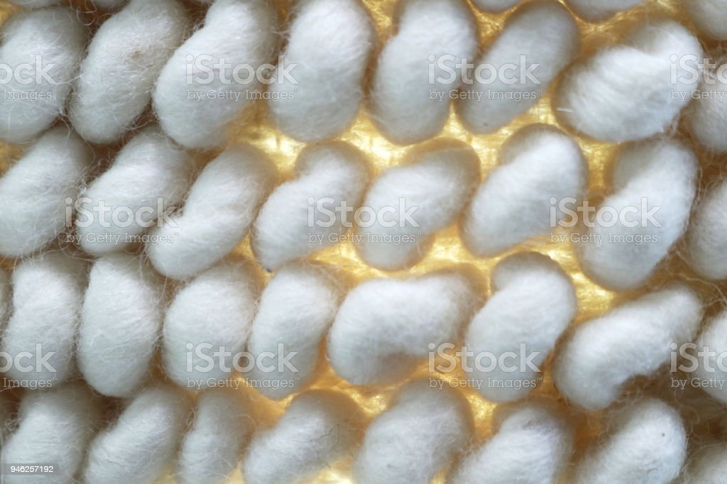 Macro of large white woven background with yellow light showing though woven fibers inbetween poofs stock photo