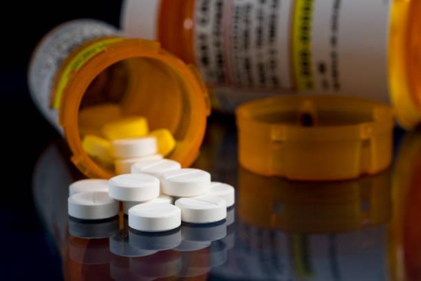 macro di compresse di oppioidi ossicodone con bottiglie da prescrizione su sfondo scuro - assuefazione foto e immagini stock