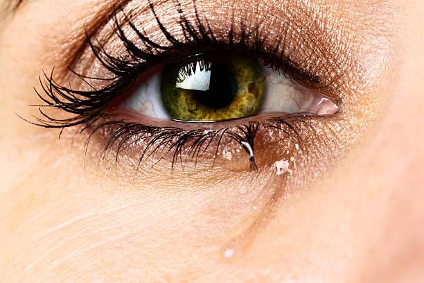 makro des einzelnen, der zu tränen gerührten eye zugehörigkeit zu sehr unglücklich frau - träne stock-fotos und bilder