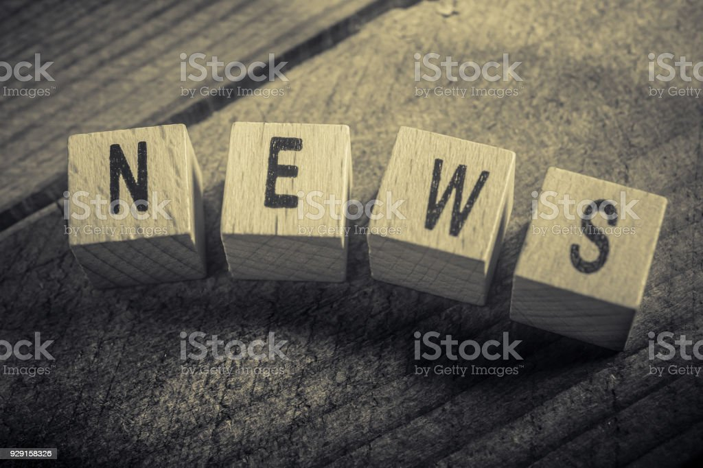 Macro Of The Word News Formed By Wooden Blocks On A Wooden Floor stock photo