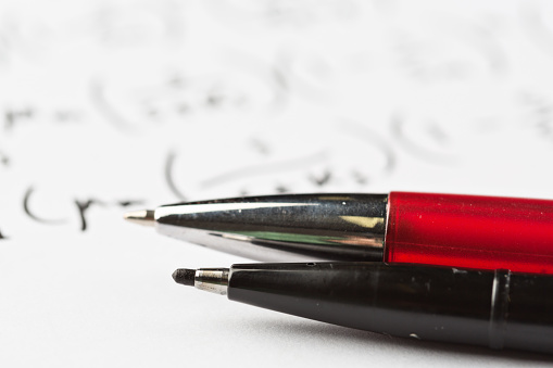 istock Macro of two pens resting on complex equation 874278938
