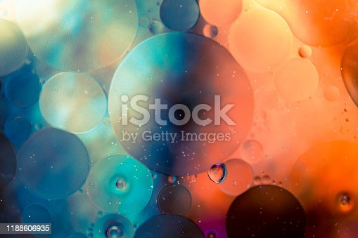 Close up macro image depicting droplets of oil in water on a multi colored background. The oil forms interesting circles and spheres in the water, and colorful background produces and abstract effect. Horizontal color image with copy space.