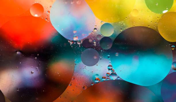 macro oil and water multi colored abstract background - glass material stock pictures, royalty-free photos & images