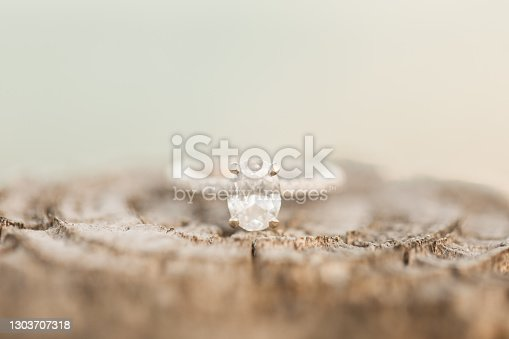 istock Macro Photo of an Oval Diamond White Gold Engagement Ring on Brown Wood on a Beach 1303707318