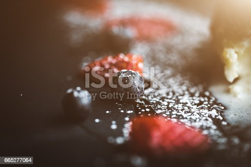502634476istockphoto Macro photo of strawberry and Blueberries on slate plate with coconut background. Food concept. Red summer fruits. Close up object. Flare copy space for text, design 665277064