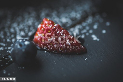 502634476istockphoto Macro photo of strawberry and Blueberries on slate plate with coconut background. Food concept. Red summer fruits. Close up object. Flare copy space for text, design 667638698