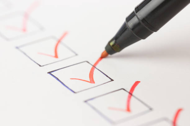 macro photography of check mark over white background - checklist stock photos and pictures