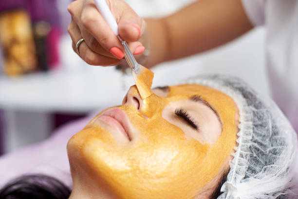 macro photography of the hand of the beautician with the help of a special brush puts on the face of the girl a golden mask in the spa - maschera foto e immagini stock