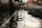 Rain in the gutter on a downtown street. Crisp detail in the areas which are in focus, and an incredibly small depth of field.