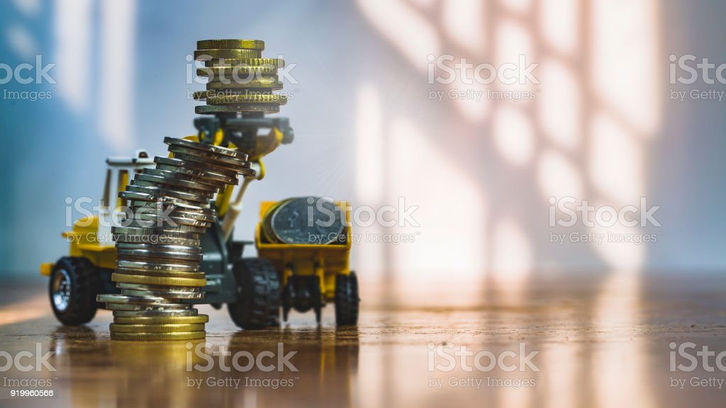 Macro shoot of major currency money including euro, us dollar and Chinese Yuan (RMB), Mixed stacked Coins, on wooden table, with blur construction machinery toy. Making money concept. Vintage tone. stock photo