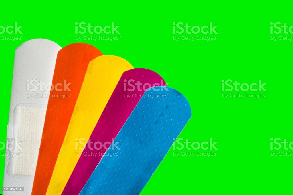 Macro shot detail of first aid dressing (Plaster) with non-stick pad for quick wound healing. Colorful set of sterile wound dressing isolated on green background with copy space for text. stock photo