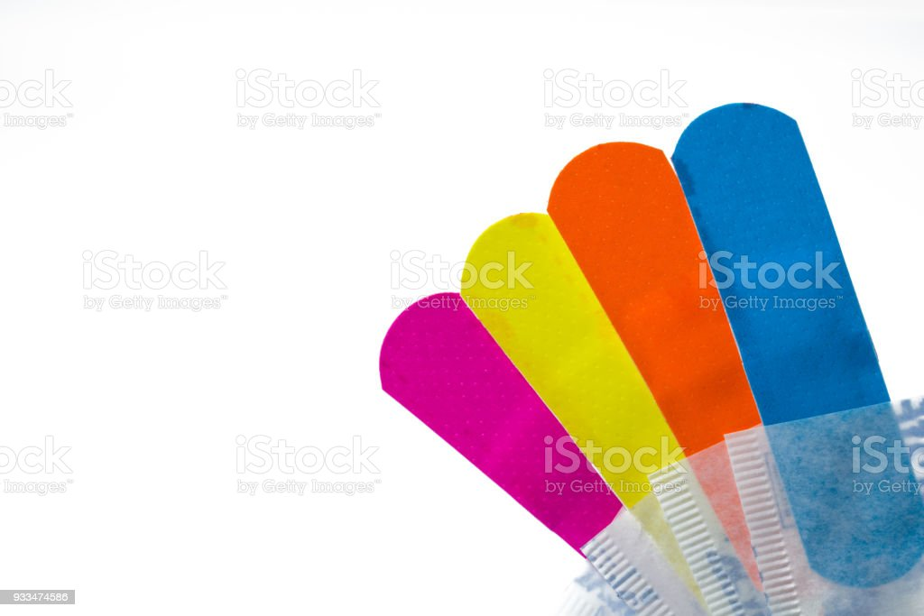 Macro shot detail of first aid dressing (Plaster) with non-stick pad for quick wound healing. Colorful set of sterile wound dressing isolated on white background with copy space for text. stock photo