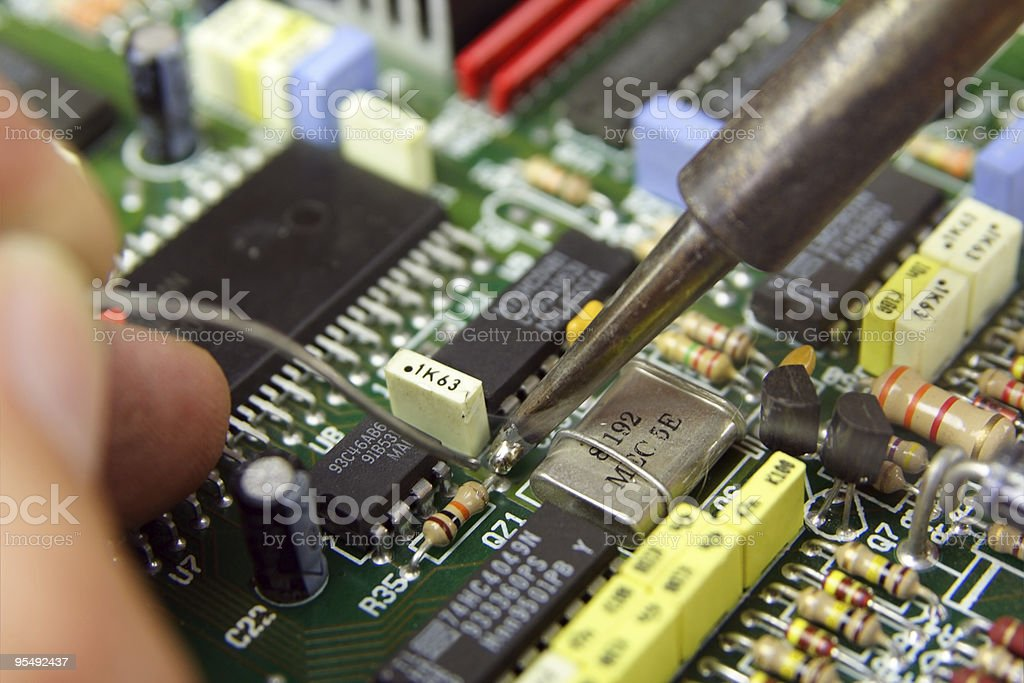 Macro shot of a technician soldering electronic components - Royalty-free Capacitor Stock Photo