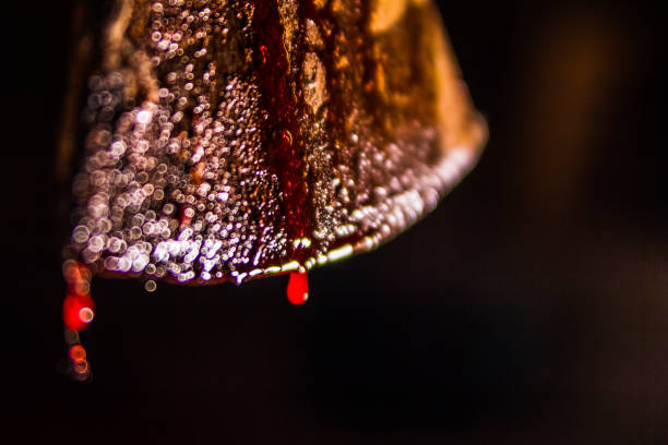 Macro shot of blood dripping from axe blade stock photo