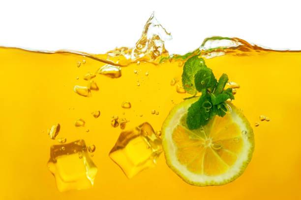 Macro shot of dipping wedges of lemon, mint leaves, ice cubes into green tea, lemonade stock photo