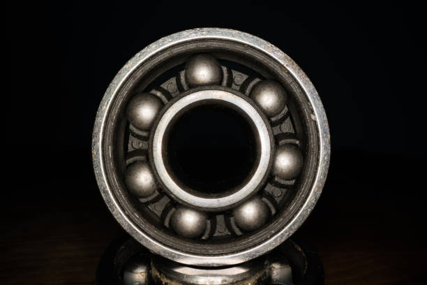 Macro shot of stainless steal bearing. New replacement roller skate bearings isolated on black background. Standard ABEC type bearing for inline skates, skateboard, long board or scooters Macro shot of stainless steal bearing. New replacement roller skate bearings isolated on black background. Standard ABEC type bearing for inline skates, skateboard, long board or scooters ball bearing stock pictures, royalty-free photos & images