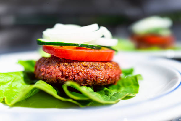 Macro side closeup of vegan meat sausage patty on plate with romaine lettuce leaf and tomatoes cucumbers onions sliced for burger healthy serving stock photo