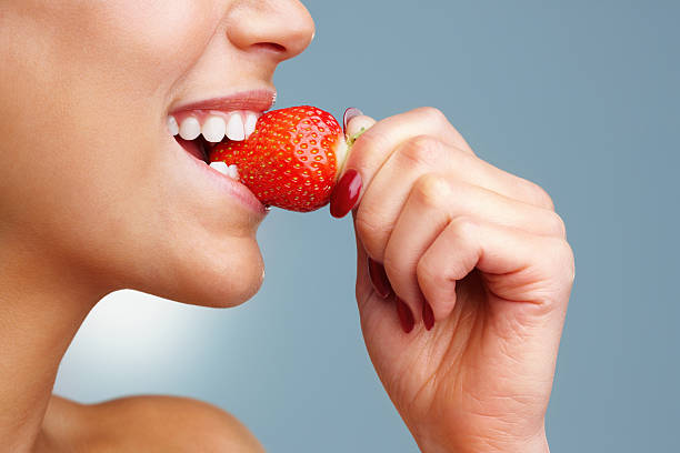 Macro view of a pretty young female eating fresh strawberry stock photo