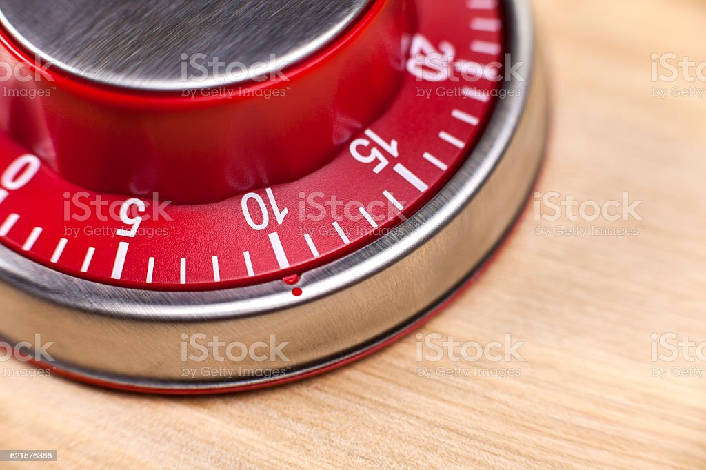 Macro view of a red kitchen timer showing 10 minutes stock photo