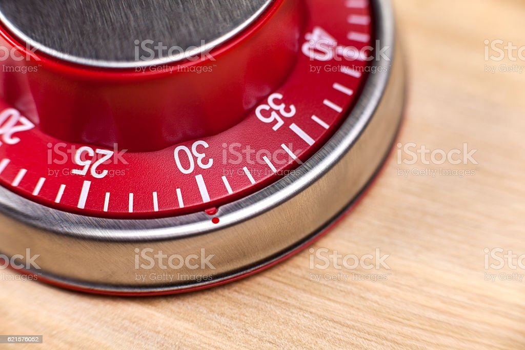 Macro view of a red kitchen timer showing 30 minutes photo libre de droits
