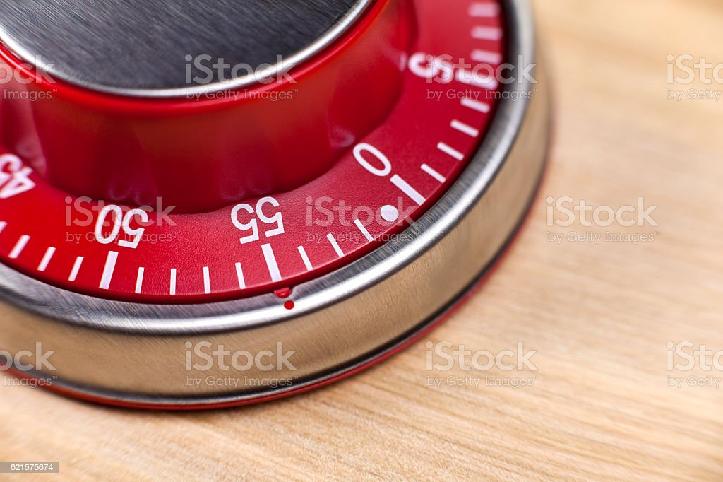 Macro view of a red kitchen timer showing 55 minutes photo libre de droits