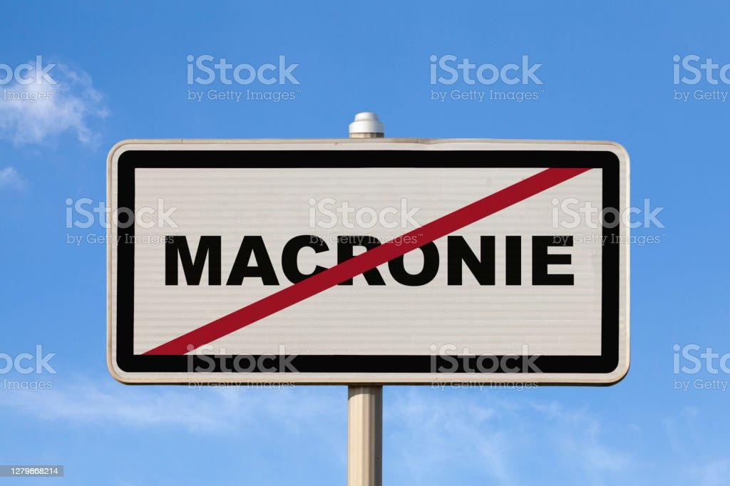 "Macronie - French exit city sign A French city sign against a blue sky indicating you're exiting ""Macronie"". Color Image Stock Photo"