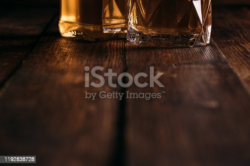 872334598 istock photo Macrophotos of a whiskey bottle in dim light on a wooden background. 1192838728