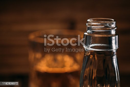 872334598 istock photo Macrophotos of a whiskey bottle in dim light on a wooden background. 1192839372