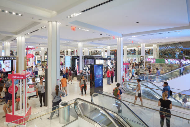 macy's department store interior, cosmetics area with escalators in new york - shopping mall stock photos and pictures