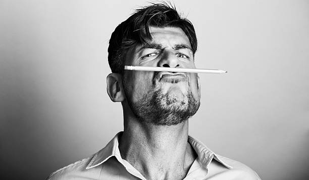 Mad artist holds a pencil with his lips stock photo