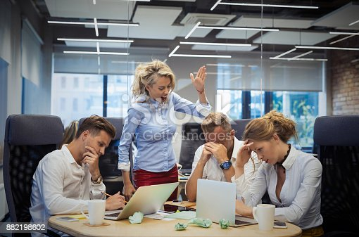 istock Mad boss showing gestures to employees 882198602