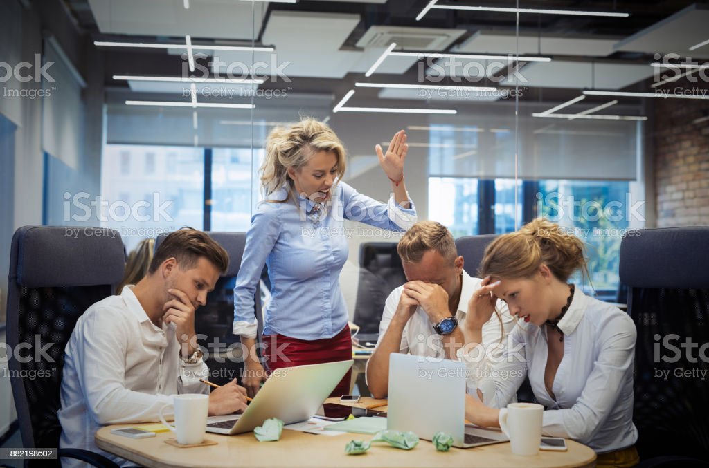 Mad boss showing gestures to employees stock photo