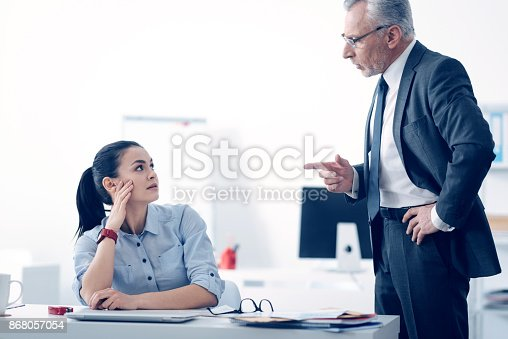 463813207 istock photo Mad businessman shouting at his young female employee 868057054