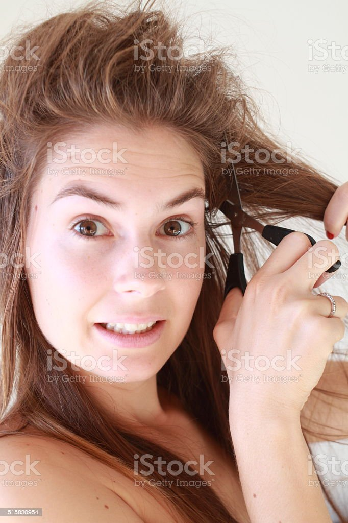 Mad girl cutting her tangled hair with scissors stock photo