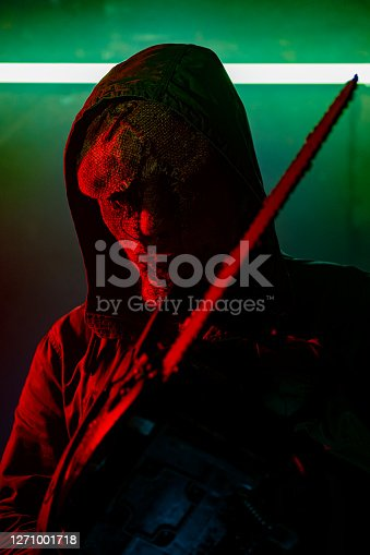 Evil man in a scary mask standing in a room with a neon light holding a chainsaw. Horror movie portrait.