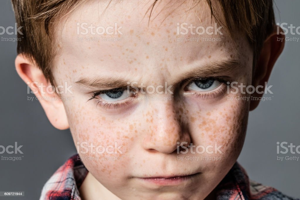mad little kid with furious blue eyes for childhood rebellion stock photo