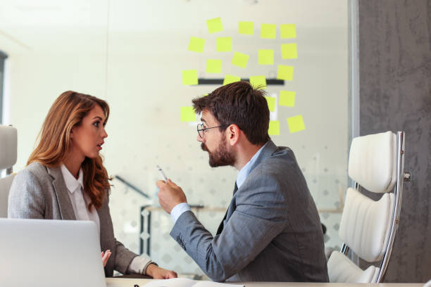 Mad male employee blaming female colleague for mistake stock photo