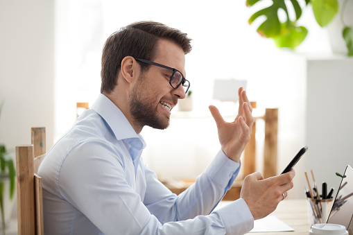 istock Mad male employee irritated by smartphone malfunction 1091487644