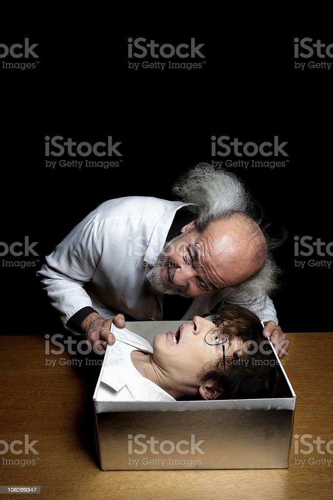Mad Male Magician Puts Subject's Head in a Box royalty-free stock photo