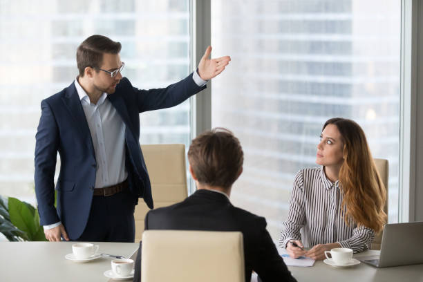 Mad male worker asking female partner leave meeting Mad male worker gesturing asking female colleague leave business meeting, angry businessman standing showing to doors having dispute with woman partner, associates argue at negotiations scolding stock pictures, royalty-free photos & images