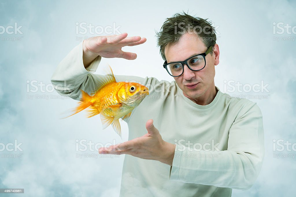 Mad Professor in smoke and goldfish, art concept of science stock photo