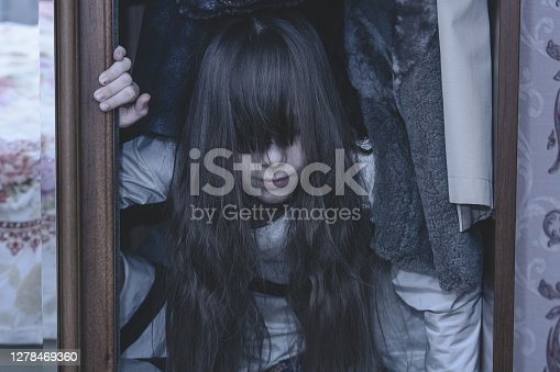 Mad scary girl in cupboard at dark night. Horror background with child possessed by devil. Demon possessed little girl in closet at night. Ghost of little girl at dark night. Child ghost in cupboard.