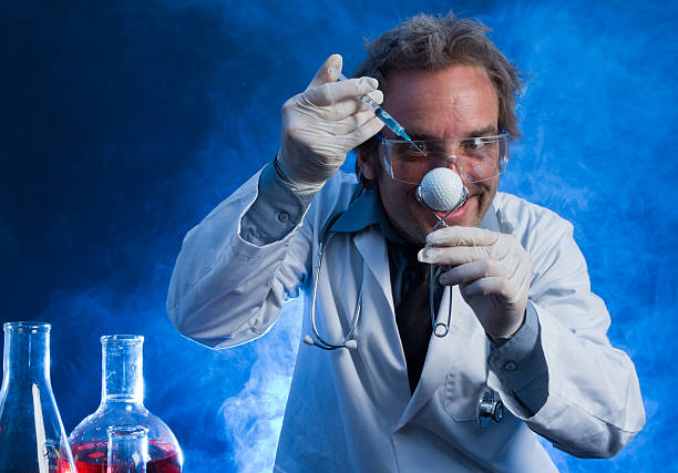 mad scientist with a golf ball and hypodermic needle - carolinemaryan stock pictures, royalty-free photos & images